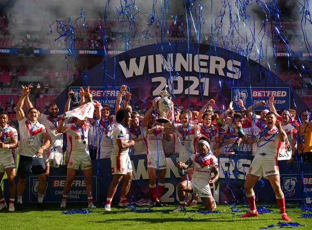 St Helens' James Roby, centre, lifts the trophy