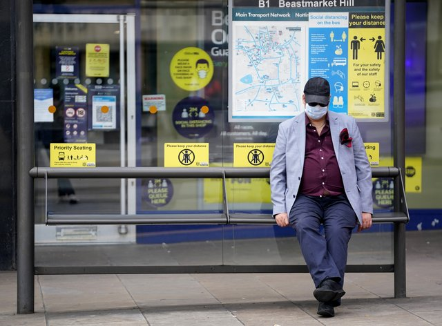 A member of the public wearing a mask sits at a bus stop