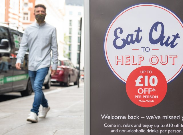 People pass a sign advertising the Eat Out to Help Out scheme last summer