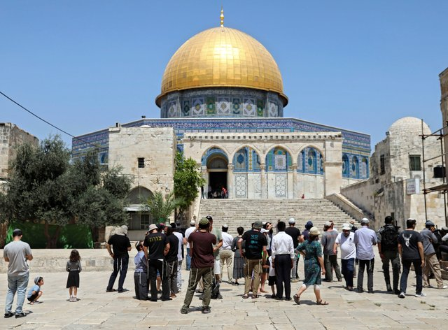 Israeli Jewish men stand at the steps leading to the Dome of the Rock Mosque in the Al Aqsa Mosque compound, during the annual mourning ritual of Tisha B'Av (the ninth of Av) (Mahmoud Illean/AP)