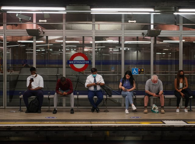 Commuters, some not wearing facemasks, at Westminster Underground station in London