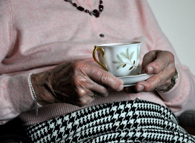 An elderly woman holding a cup of tea. (Kirsty O'Connor/PA)