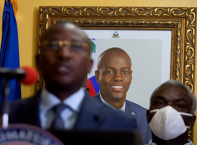 A picture of late Haitian President Jovenel Moise hangs on the wall of his former residence, behind interim prime minister Claude Joseph (Joseph Odelyn/AP)
