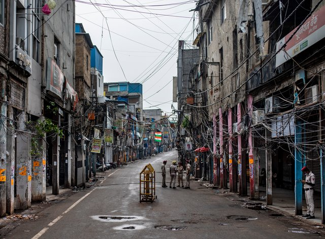 Indian Home Guard personnel stand in an empty street of Sadar Bazar wholesale market which is partially closed for violating Covid-19 guidelines (Altaf Qadri/AP)