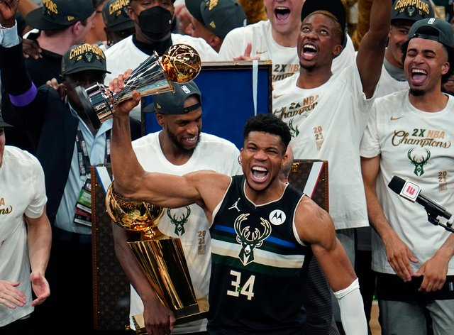 Milwaukee Bucks forward Giannis Antetokounmpo (34) holds the finals MVP trophy after the Bucks defeated the Phoenix Suns in Game 6 of basketball's NBA Finals