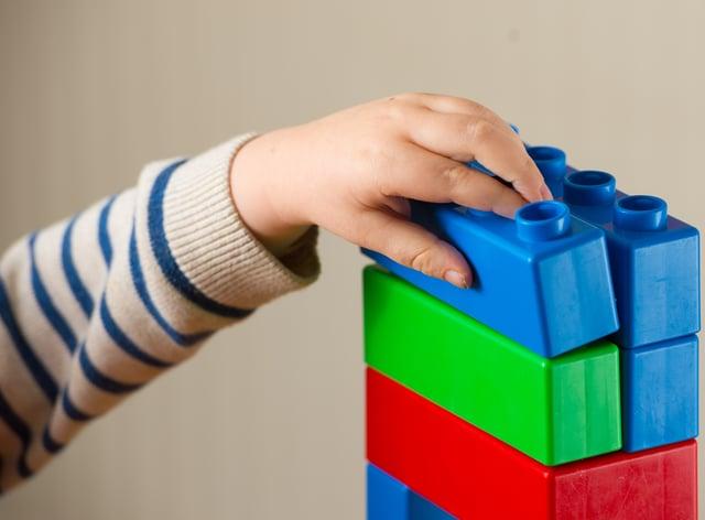 A preschool age child plays with plastic building blocks