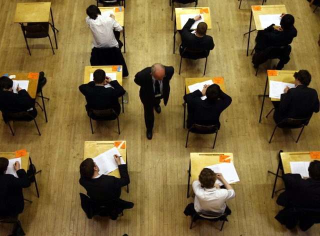 Pupils sitting at desks in an exam hall