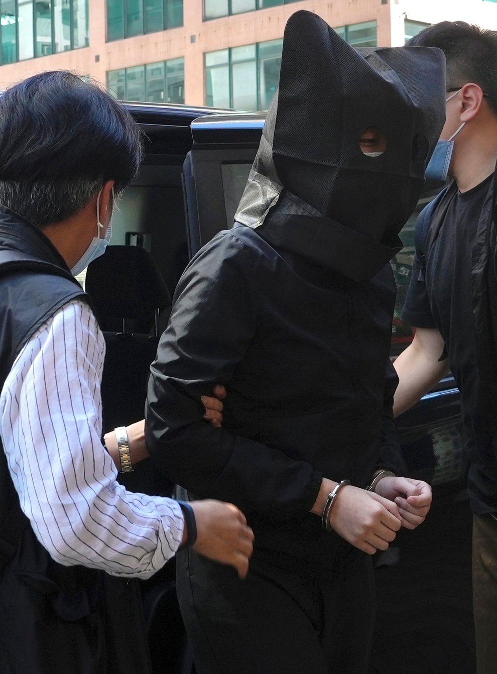 A hooded suspect is accompanied by police officers to searchfor evidence at an office in Hong Kong (Vincent Yu/AP)