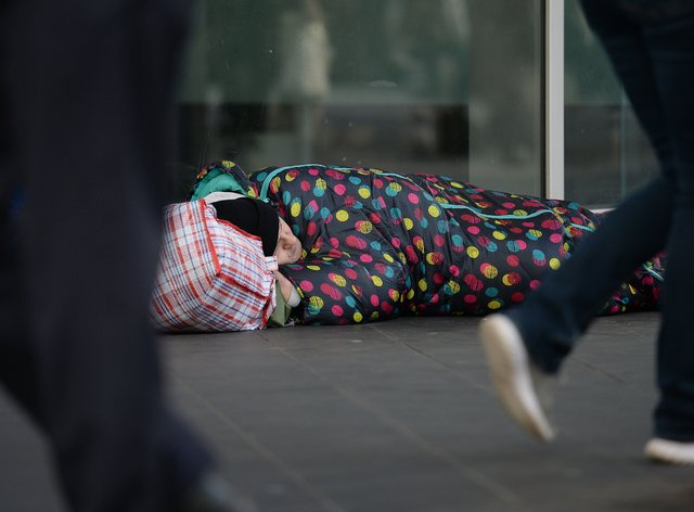 People walking past a homeless man in London (Nick Ansell/PA)
