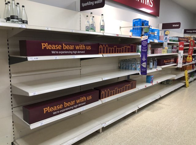 Empty shelves and signs on the soft drinks aisle of a Sainsbury's store in Blackheath, Rowley Regis in the West Midlands. Supermarkets have urged customers not to panic buy (PA)