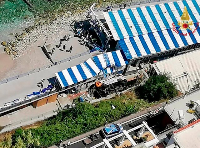 A bus lies on its side after crashing through a guardrail, on the island of Capri, Italy, Thursday, July 22, 2021. A public bus on the Italian vacation island of Capri crashed through a guardrail and landed on a beach resort area Thursday, fatally injuring the driver, firefighters and Capri's mayor said (Italian Firefighters via AP)