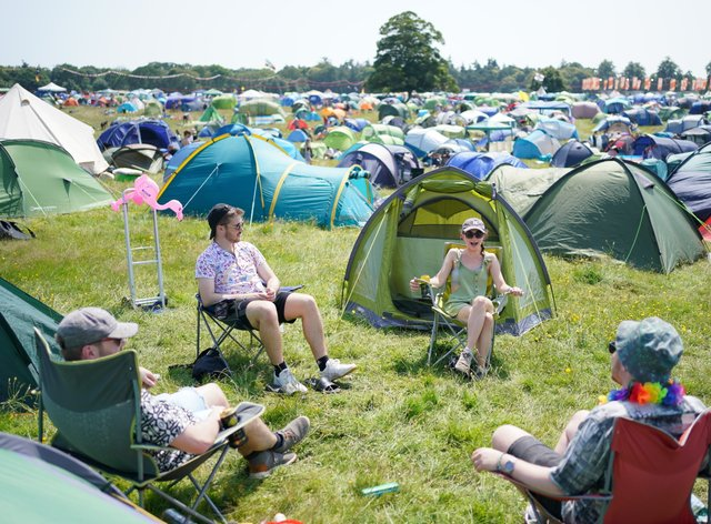 Festivalgoers sit amongst their tents at the Latitude festival in Henham Park, Southwold, Suffolk. Picture date: Thursday July 22, 2021.
