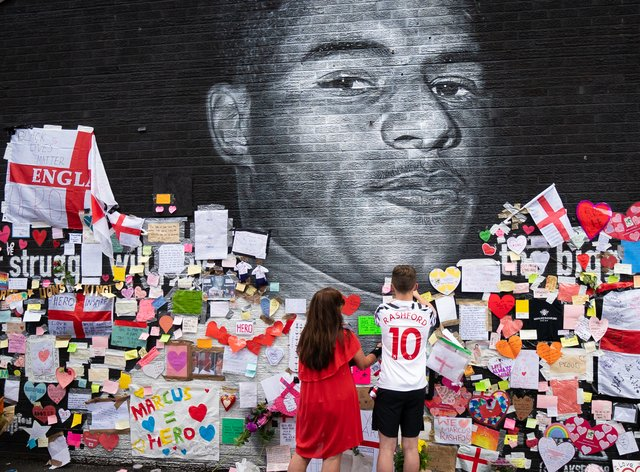 Mackenzie Robertson and his mother Sally Coles-Robertson put up a message on the mural of Manchester United striker and England player Marcus Rashford in Withington (Danny Lawson/PA)