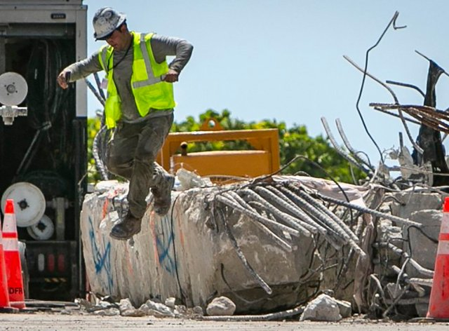 A worker jumps off a large piece of rubble on the site of the Champlain Towers South collapse, in Surfside, Fla., Monday, July 19, 2021. Two close friends and former New Yorkers are among the last of the missing as the South Florida condo search stretches into a fourth week. (Jose A Iglesias/Miami Herald via AP)