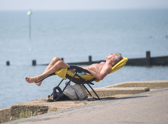 A man enjoys the sun by Southend beach in Essex (PA)