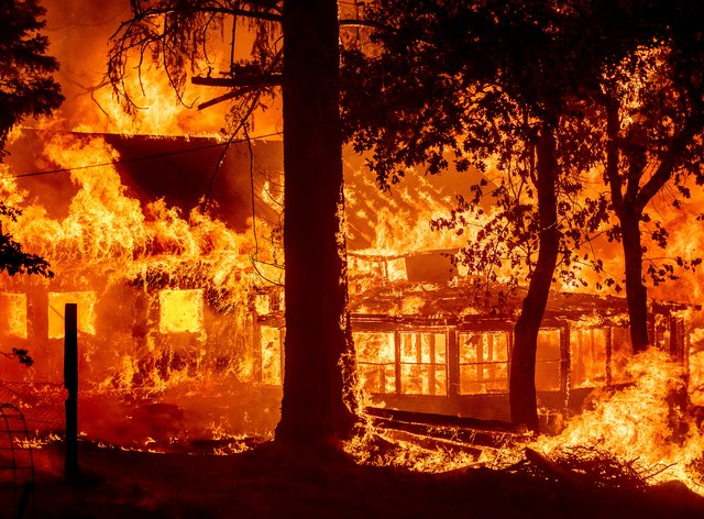 Flames from the Dixie fire consume a home in the Indian Falls community of Plumas County, California (Noah Berger/AP)