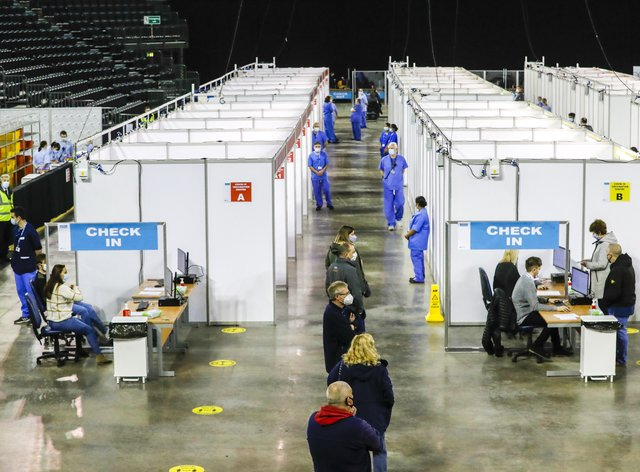 People queue to receive Covid-19 vaccines at the vaccination centre in the SSE Arena in Belfast (Liam McBurney/PA)