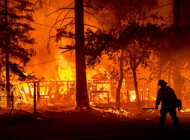 A firefighter passes a burning home as the Dixie Fire flares in Plumas County, Calif., Saturday, July 24, 2021. The fire destroyed multiple residences as it tore through the Indian Falls community. (AP Photo/Noah Berger)