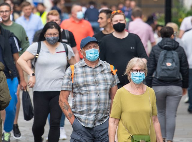 People wearing face masks among crowds of pedestrians in London (Dominic Lipinski/PA)