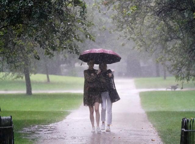 Two women walk through heavy rain (Victoria Jones/PA)