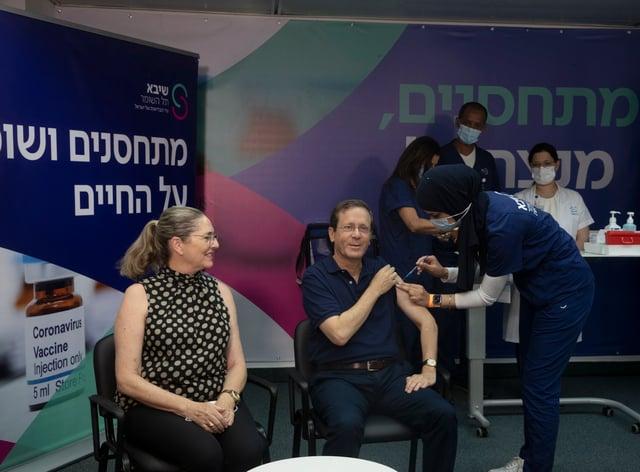 Israeli president Isaac Herzog receives his booster jab (Maya Alleruzzo/AP)