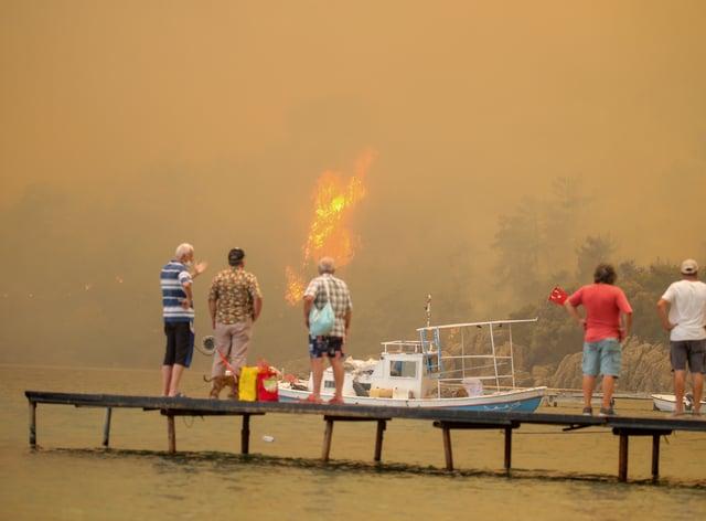 Tourists wait to be evacuated from a smoke-engulfed beach in Turkey (AP Photo/Emre Tazegul)