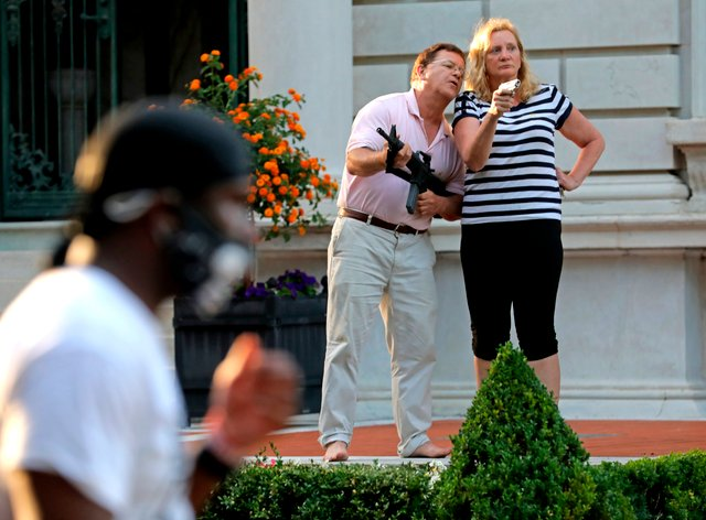 Mark and Patricia McCloskey standing in front their house confront protesters in St Louis (Laurie Skrivan/St. Louis Post-Dispatch via AP)