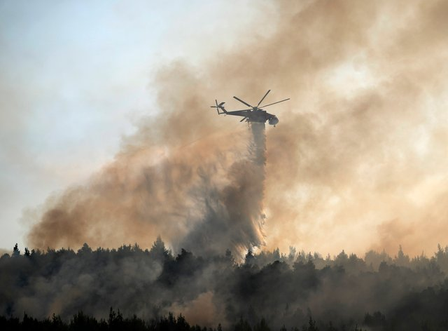 An helicopter drops water over a fire in Varibobi area, northern Athens, Greece, Wednesday, Aug. 4, 2021. Firefighting planes were resuming operation at first light Wednesday to tackle a major forest fire on the northern outskirts of Athens which raced into residential areas the previous day, forcing thousands to flee their homes amid Greece's worst heatwave in decades. (AP Photo/Thanassis Stavrakis)