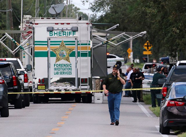 Officials at the scene of the shooting (Michael Wilson/The Ledger/AP)