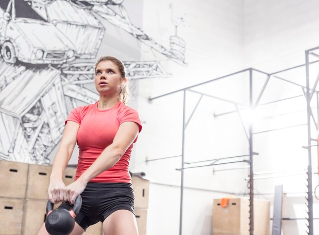 Woman lifting kettlebell in crossfit gym (Alamy/PA)