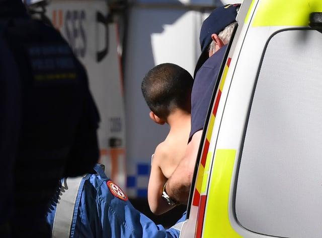 Three-year-old AJ Elfalak is carried by a paramedic (Dean Lewins/AAP Image via AP/PA)