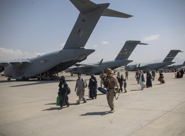 UK armed forces lead Afghan evacuees to a plane at Kabul airport (LPhot Ben Shread/MoD/PA)