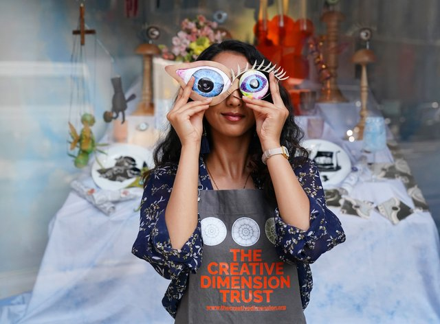 Student Roshni Patel holds two pieces of artwork in front of her eyes (Jonathan Brady/PA)