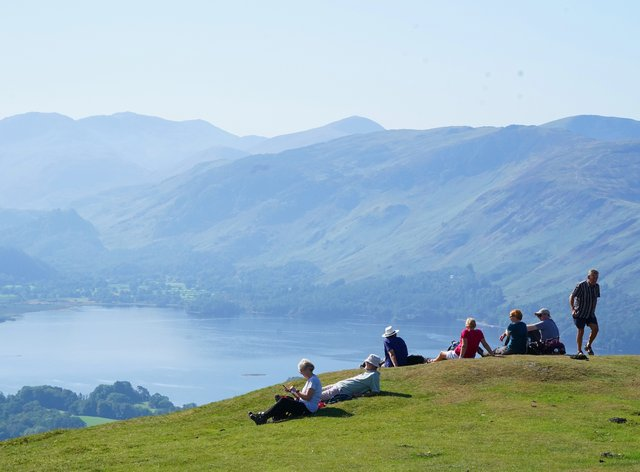 Walkers take in the view of Derwent Water in Cumbria (PA)