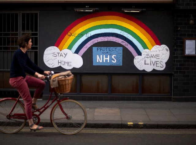 A woman cycles past a rainbow graffiti in support of the NHS in Soho (PA)