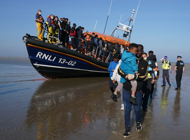 A group of people thought to be migrants are brought ashore at Dungeness in Kent (Gareth Fuller/PA)