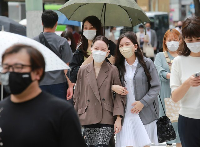 People wearing face masks to protect against the spread of coronavirus walk on a street in Tokyo (Koji Sasahara/AP)