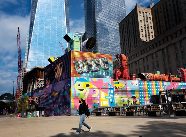 A woman walks by the colourful murals that surround the foundation for 2 World Trade Centre in New York (AP Photo/Mark Lennihan)