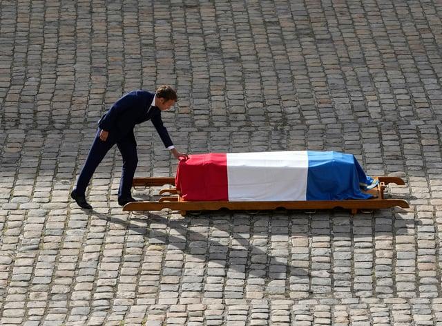 French President Emmanuel Macron touches the coffin of Jean-Paul Belmondo (Michel Euler/AP)