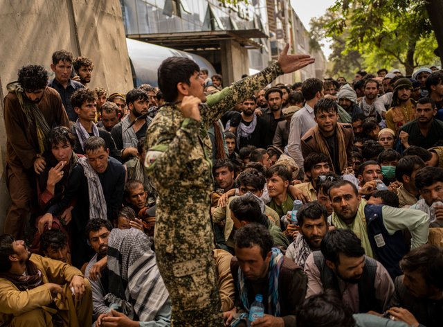 Afghans wait in front of a bank as they try to withdraw money in Kabul, on Sunday. The UN has expressed deep concerns over a growing humanitarian crisis in the country (Bernat Armangue/AP)