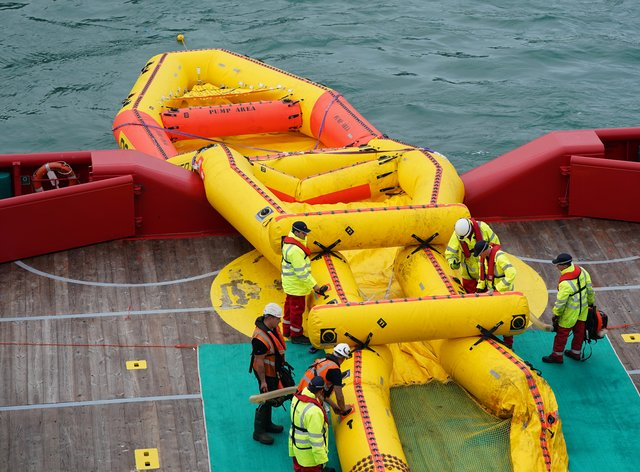 Members of the Maritime and Coastguard Agency deploy a giant inflatable counter-pollution kit named the Current Buster 6 (Andrew Matthews/PA)